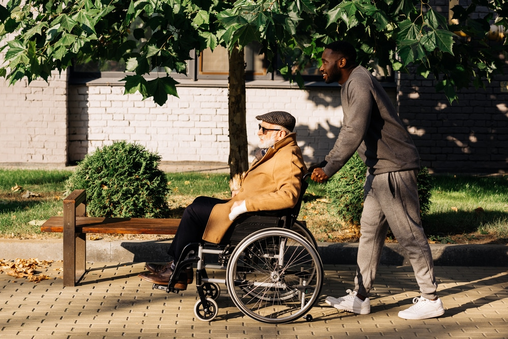man being pushed in wheelchair